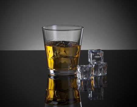 ices: whiskey glass and ace with ices on a dark background