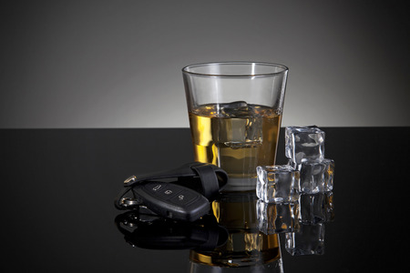hard liquor: A car key in the foreground and glass of whiskey behind.