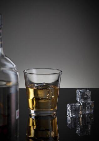ices: whiskey bottle and glass with ices on a dark background