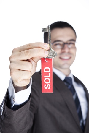 sold sign: Realtor Holding Up Old Key with Red SOLD Sign