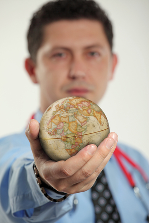 global health: Doctor holding the world in his hands. Concept for global health, diseases, disasters, events, being careful when traveling and similar. Stock Photo