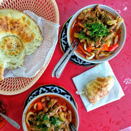 Traditional asian noodle soup with vegetables and meat, known as lagman. Oriental, uzbek style cuisine. A bowl of lagman with pita, uzbekistan bread