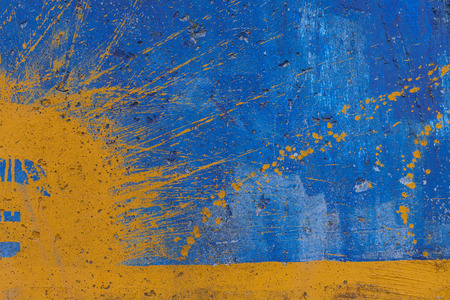Yellow spray on blue painted wall Imagens
