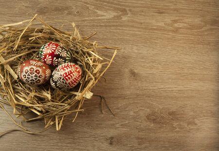 easter nest: Easter eggs in nest on wooden background