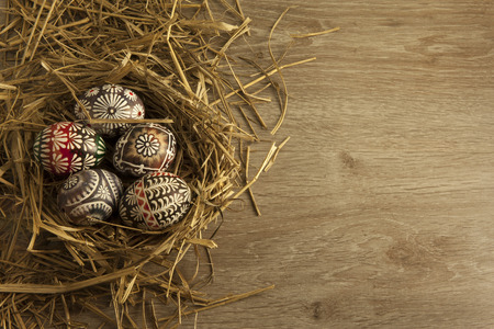 Easter eggs in nest on wooden background photo