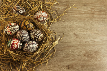april flowers: Easter eggs in nest on wooden background