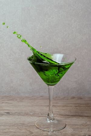 Splash in glass of green alcoholic cocktail drink with lime, mint and ice cube on gray gradient background 写真素材
