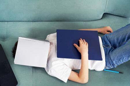 distance learning at home with students . students study at home.a schoolboy sleeps at home from fatigue from lessons 版權商用圖片