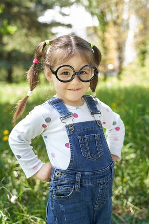 a healthy girl with two pigtails and glasses stands with her hands on her hips. 版權商用圖片