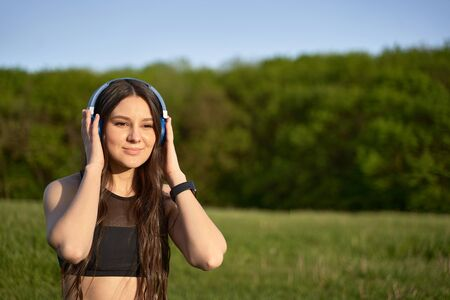 athletic healthy girl listening to music with headphones in nature Фото со стока - 147074705