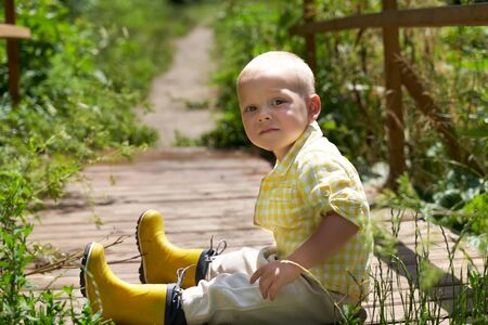 a funny little boy in yellow rubber boots sits on the bridge.