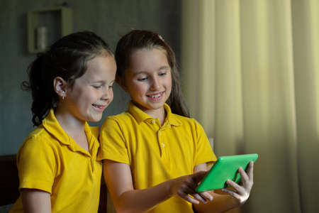 two little girls look at the tablet and laugh.