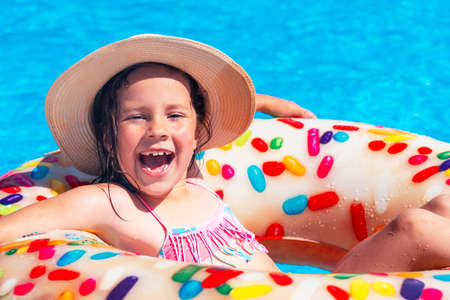 a little beautiful girl in a hat is bathing in a swimming circle in the pool. sea. the sun. beach Stockfoto