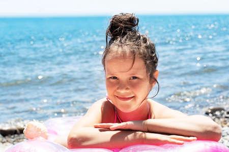 a beautiful little girl is lying on a bathing mattress near the sea.