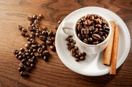 coffee beans in a coffee cup with cinnamon sticks. Top view