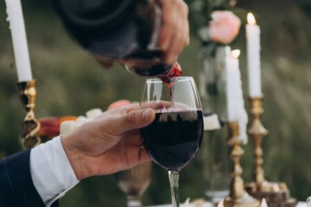 male hand pours wine into a glass at a romantic candlelight dinner, outside