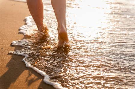 Feet girls walk on the sand along the sea. No peaple