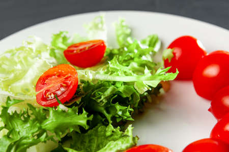 salad with lettuce and tomatoes, preparation of salad ingredients in the process of cooking
