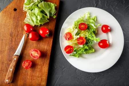 Diet and the process of making a salad in the process of the knife lies on a wooden board with cherry tomatoes and lettuce greens, flat lay and top view. Grey and dark background 写真素材