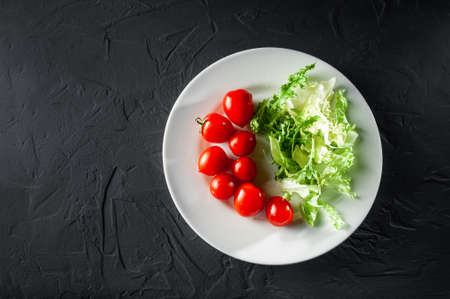 Empty text writing space cherry tomatoes with lettuce on a white plate on a gray dark background