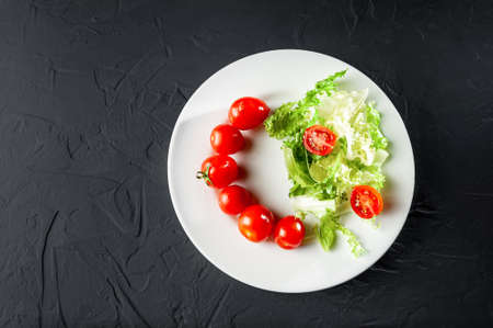 cherry tomatoes with lettuce on a white plate on a gray dark background 写真素材