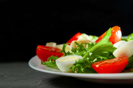 salad with cherry tomatoes and quail eggs on a white plate on a gray background view from above