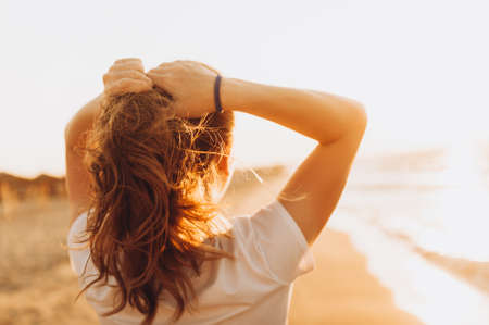 Girl looks at the sunset at the sea