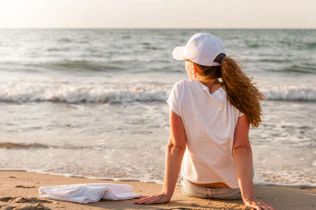 the athlete sits on the beach after a jog and looks at the sunset. Girl in white T-shirt and cap Archivio Fotografico - 150760933
