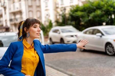 young girl in a yellow shirt and blue jacket. Bright beautiful woman stops and causes a taxi raising her hand