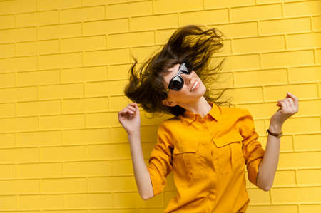 happy young girl in sunglasses against a bright yellow wall. Sunny and summer mood