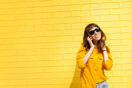 Girl on the phone was told the happy news Girl in yellow shirt against the yellow wall, talking on the phone. Copy space
