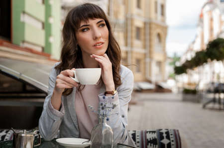 Beautiful young woman with coffee cup looking away at coffeeshop 版權商用圖片
