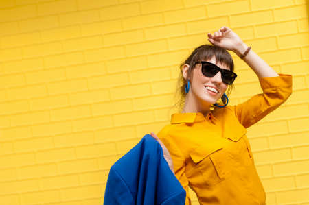 Happy girl on a yellow background. A girl in sunglasses, a yellow shirt and a blue jacket stands against the wall and smiles