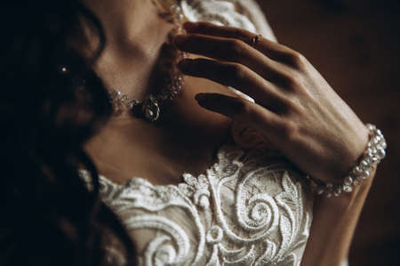 Portrait of the bride. The young bride holds on to the pendant around her neck. The brides face is hidden only in the chest and arm