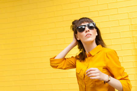 Young girl on bright yellow background in yellow shirt straightens her hair