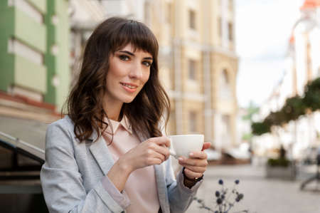 Girl with a cup of coffee sits in a cafe and looking into the camera