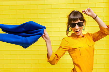 Cheerful girl brandishes a blue jacket against the yellow wall. Happy girl in bright colors enjoys life Archivio Fotografico