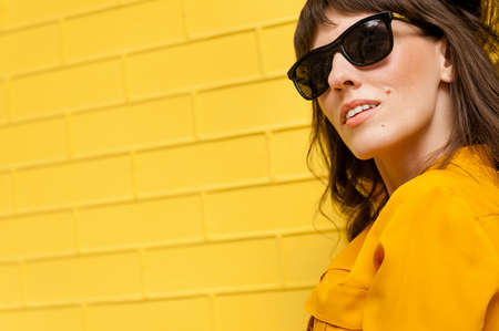 beautiful girl in a yellow shirt against the yellow wall. There is an empty space for inscription and text