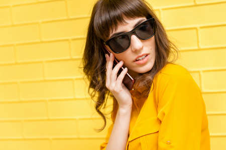 portrait of a girl in a yellow bun against the yellow wall. Devushka speaks on the phone and looks away
