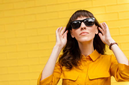 portrait of a girl in sunglasses against the yellow wall. Empty place to write text