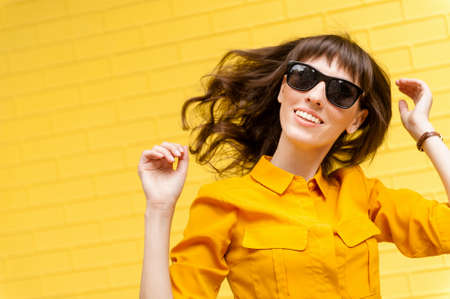 happy girl in bright clothes on a yellow background enjoys life. Girls hair develops in the wind