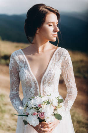Bride with a bouquet of flowers against the backdrop of the mountains