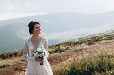 Bride with a bouquet of flowers in her hands stands against the backdrop of the mountains and smiles