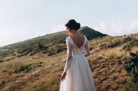 Stylish bride standing back on beautiful landscape of mountains on sunset