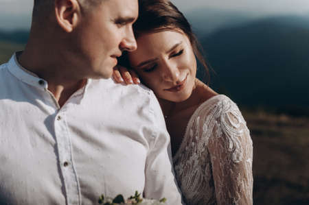 Beautiful wedding couple in the mountains. Bride and groom stand side by side and hug Archivio Fotografico