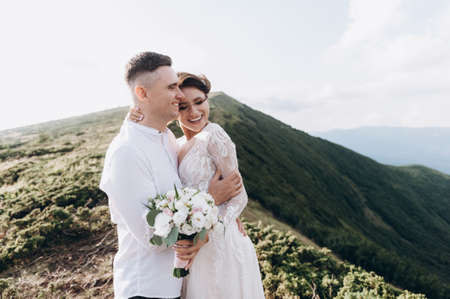 newlyweds cuddle against the backdrop of the mountains