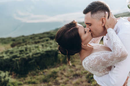 Kissing wedding couple staying over beautiful landscape Archivio Fotografico