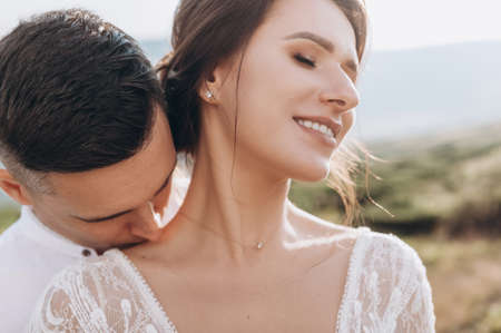 The groom kisses the bride on the shoulder. Sensual portrait of young elegant just married pair