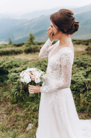 Bride with a bouquet of flowers laughs against the backdrop of the mountains