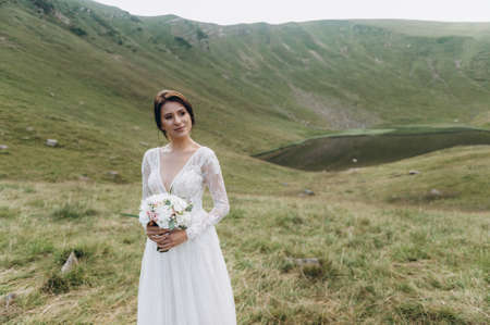A young bride in a wedding dress with a bouquet of flowers in her hands. Against the backdrop of the lake and the mountains
